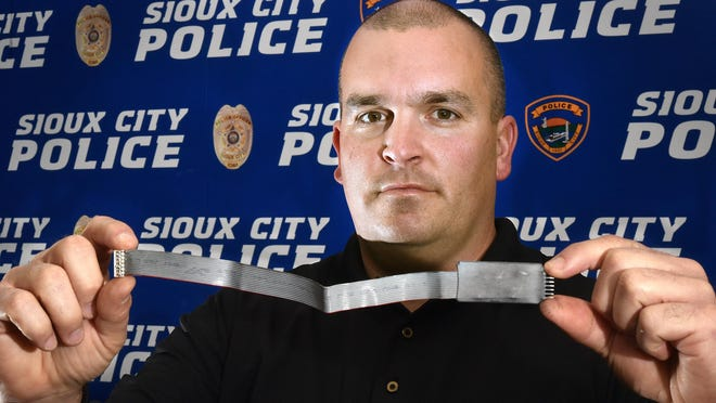 Sgt. Chris Grovesm of the Sioux City (Iowa) Police Department displays a credit card skimming device that was recently found inside a gas station's pump.