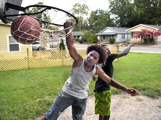 Cornelius Starnes,15, and Angelo Nelson,18, play basketball