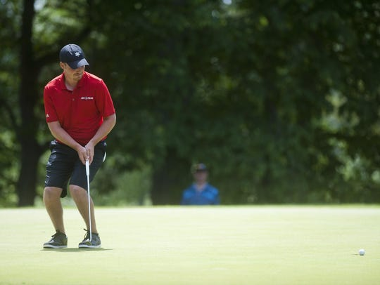 Bryan Smith reacts as his putt clips the cup but doesn't