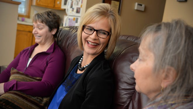 Tammy Moore, center, talks with sisters, Joan Willenbring, right, and Pam Hansen at Hansen's home Nov. 18 about their decisions to get mastectomies and hysterectomies after a history of breast and ovarian cancer in their family.