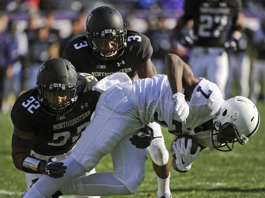 Penn State wide receiver Geno Lewis (7) is stopped by Northwestern cornerback Keith Watkins II (3) and linebacker Nate Hall (32)  during Saturday's game  in Evanston, Ill. Penn State lost 23-21.