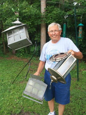 Duane Radeke holds the remnants of feeders destroyed by a bear at his home south of St. Cloud.