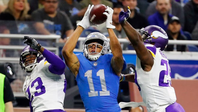 Lions receiver Marvin Jones, guarded by Vikings cornerbacks Terence Newman (23) and Xavier Rhodes, catches a 43-yard touchdown in the second half Thursday, Nov. 23, 2017 in Detroit.