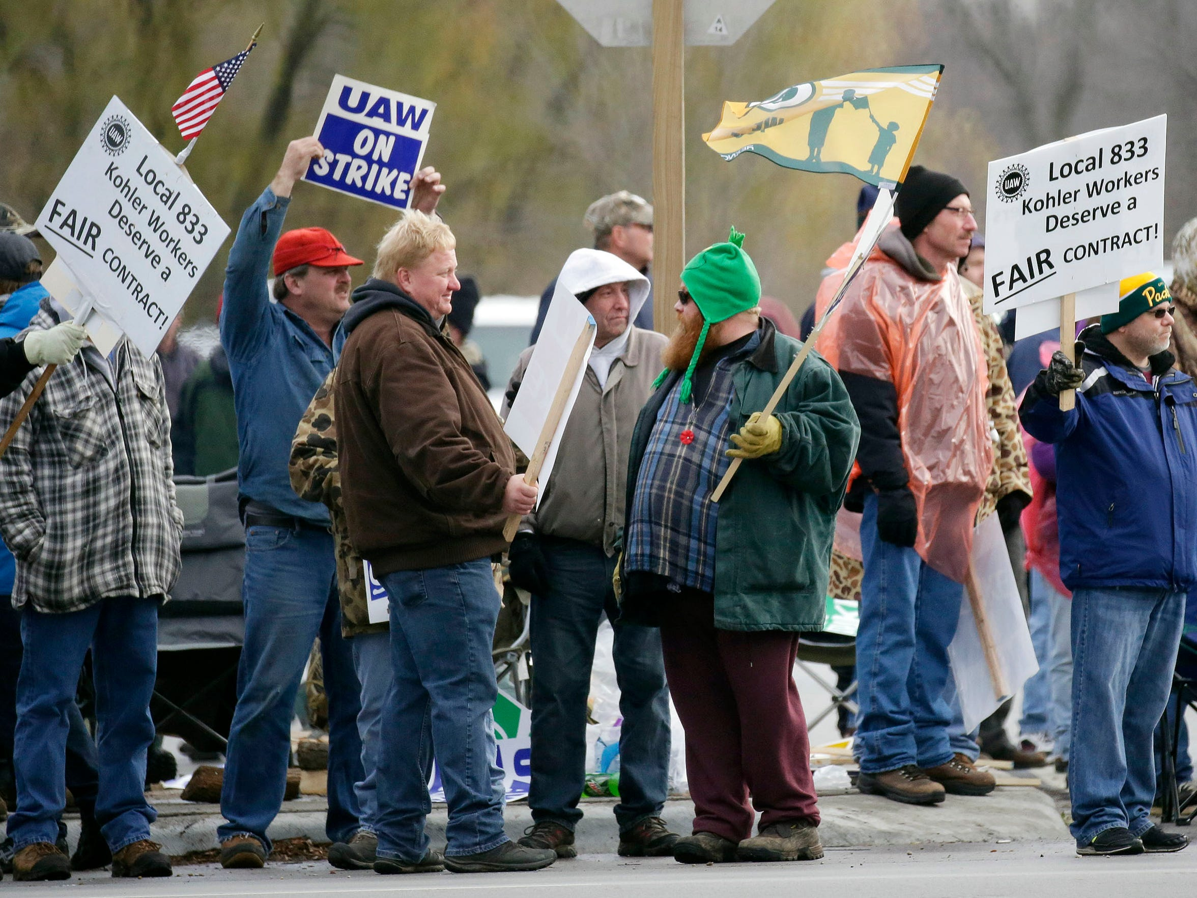 Striking members of UAW Local 833 stand in a picket line along Highland Avenue Tuesday November 17, 2015 in Kohler.
