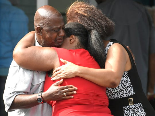 Ieshea White and Kimberly Stallworth embrace their uncle and brother Roger Bracey, who was at Burnette Chapel Church of Christ when shots were fired Sunday, Sept. 24, 2017, in Antioch, Tenn. They were reunited at another nearby church.