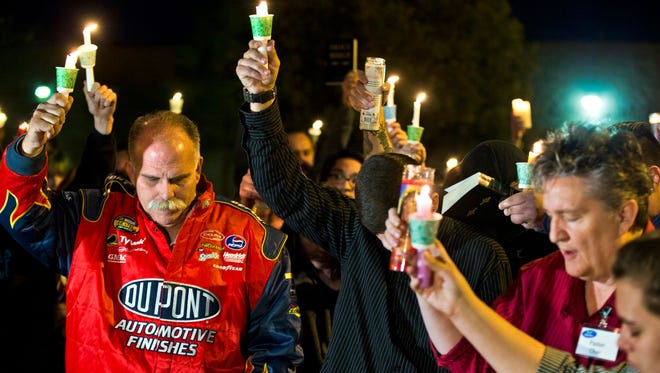 In this Tuesday, Feb. 17, 2015, photo, Robert Meyers, left, and others bow their heads during a prayer at a candlelight vigil for his wife, Tammy, who was taken off life support on Saturday after a shooting in Las Vegas. What police first described as a road rage-inspired shooting of an innocent mother of four has morphed into a more complex scenario, prompting a backlash Wednesday against the Las Vegas family and the way the case is being handled.