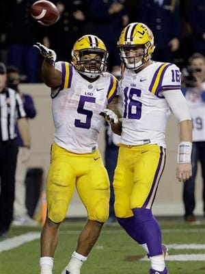 LSU running back Derrius Guice (5) tosses the ball to an official as he celebrates his touchdown with quarterback Danny Etling (16) during the second half of an NCAA college football game against Texas A&M Thursday, Nov. 24, 2016, in College Station, Texas. LSU won 54-39. (AP Photo/David J. Phillip)