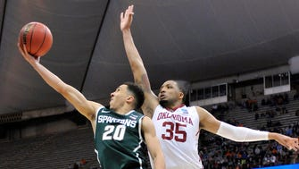 Michigan State Spartans guard Travis Trice (20) shoots the ball against Oklahoma Sooners forward TaShawn Thomas (35) during the second half in the semifinals of the east regional of the 2015 NCAA Tournament.