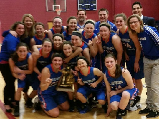 Members of Ladywood's basketball team pose with their Class B district-championship trophy.