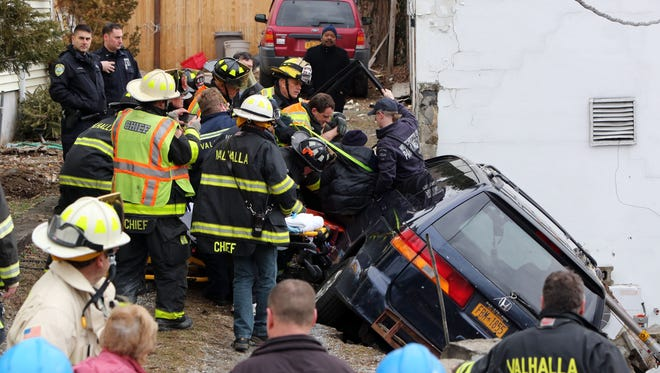 First responders remove a driver from a minivan that hit a retaining wall and collapsed into the parking lot of an auto body shop, Jan 23. 2017 in Valhalla. Firefighters from Valhalla and North White Plains and Valhalla Volunteer Ambulance Corps and Westchester EMS were on scene.