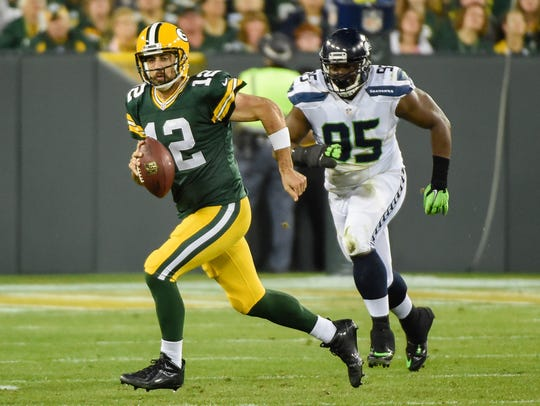 Green Bay Packers quarterback Aaron Rodgers (12) scrambles