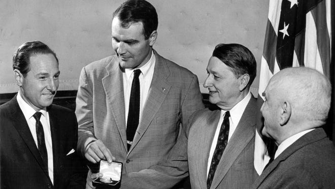 """Fred Goldsmith (left) received the kudos for his brother, Jack Goldsmith (not shown), on March 4, 1960, when the National Conference of Christians & Jews honored the latter at the Claridge Hotel. Admiring the medallion, which accompanied the citation, were (from left) Mayor Henry Loeb, Everett Cook and former mayor Walter Chandler. Mr. Goldsmith was snowbound in New York and unable to attend. The NCCJ citation described Jack Goldsmith as a """"merchant, philanthropist, soldier, president of Goldsmith's and (who) has supported the National Conference objectives, giving of his time and means."""""""