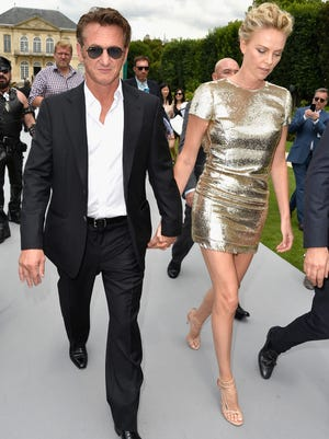 Sean Penn and Charlize Theron attend the Christian Dior show as part of Paris Fashion Week - Haute Couture Fall/Winter 2014-2015 on July 7, 2014 in Paris, France.