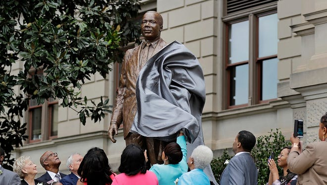 """A statue paying tribute to civil rights leader Martin Luther King Jr. is unveiled on the state Capitol grounds in Atlanta, Monday, Aug. 28, 2017. The statue's unveiling Monday came more than three years after Georgia lawmakers endorsed the project. A replica of the nation's Liberty Bell tolled three times before the 8-foot (2.44-meter) bronze statue was unveiled on the 54th anniversary of King's """"I Have a Dream"""" speech at the march on Washington."""