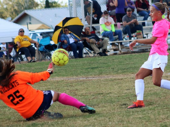 Alamogordo's Sheyenne Drake sends a ball past Deming goalkeeper Palmeria Valentine.