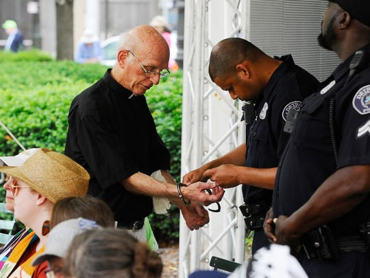 Father Tom Lumpkin  is handcuffed after he and other protesters were arrested for blocking the QLine and a downtown building. (Daniel Mears, The Detroit News)