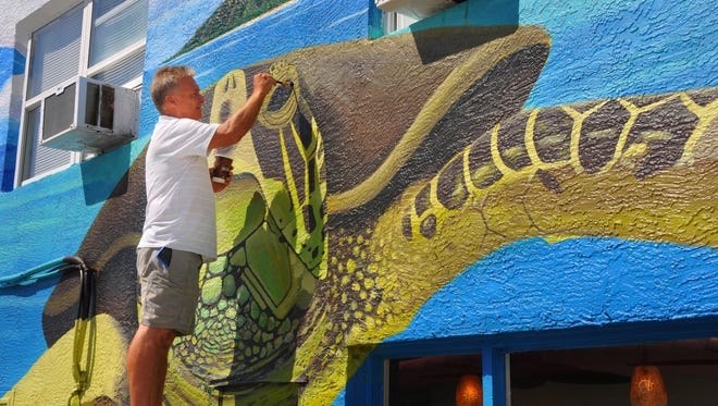 Mural artist Mike McCloskey works on a giant sea turtle mural on the east wall of Fat Kahunas restaurant in Cocoa Beach on Minutemen Causeway. This is just one of many artistic murals popping up around the Space Coast.