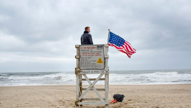 While strong, gusty winds arrive at the Oceanfront, Virginia Beach Lifeguard David Derrick tends to his duties on Friday, July 4, 2014, in Virginia Beach, Va.