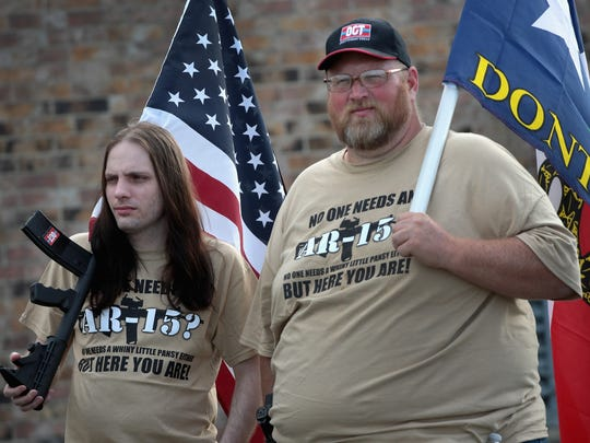 "Gun rights advocates stage a counter-protest near a March for Our Lives rally on March 24, 2018, in Killeen, Texas. These two wear T-shirts reading: ""No one needs an AR-15? No one needs a whiny little pansy either but her you are."""