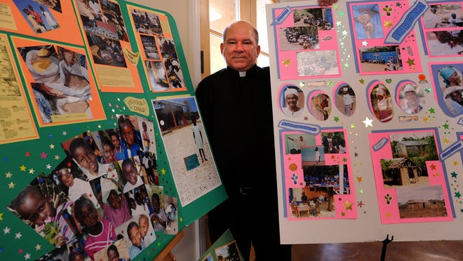 Rev. Glenn Meaux of Abbeville with two of his photo-boards that he uses when he gives talks on his mission in the mountains of Haiti.
