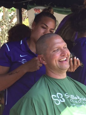 Toni Pressley, with Orlando Pride, shaves the head of Lt. Shannon McNally with Brevard County Fire Rescue on Saturday.