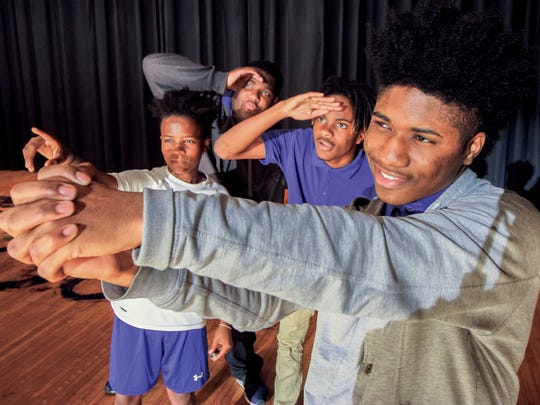 "In this Nov. 9, 2017 photo, Josh Davis, foreground, pretends to swing a bat as he plays the part of Emmett Till dreaming of being a star athlete, as his companions portrayed by Kalireon Alford, left, Isaiah Watkins and Kwame Bell look on. in Meridian, Miss. Students at Meridian High School present the play ""Tell My Story: The Death of Emmett Till,"" a dramatic rendering of the events and death of Till, a 14-year boy who was killed in 1955 Mississippi for allegedly whistling at a white woman."