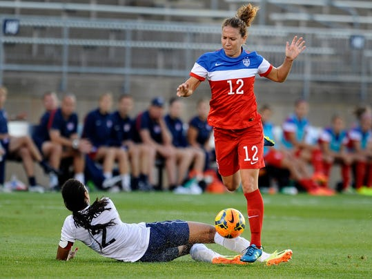 United States' Lauren Holiday, right, trips over France's Wendie Renard, left, during the first half of a women's friendly soccer match on Thursday, June 19, 2014, in East Hartford, Conn. (AP Photo/Jessica Hill)