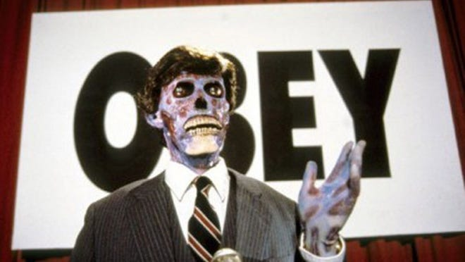 """Caption: Aliens and their subliminal messages are taking over in John Carpenter's sci-fi horror classic, """"They Live."""""""