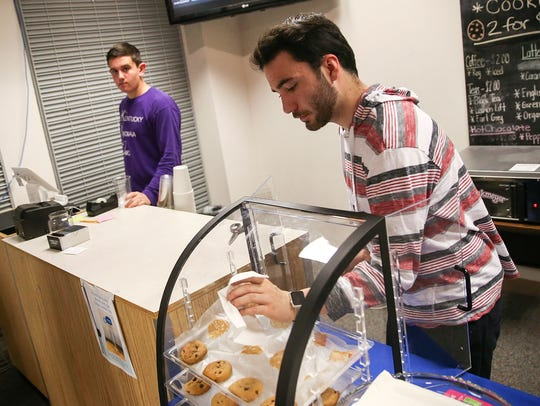 At right, senior Ethan Perkins, 18, serves cookies