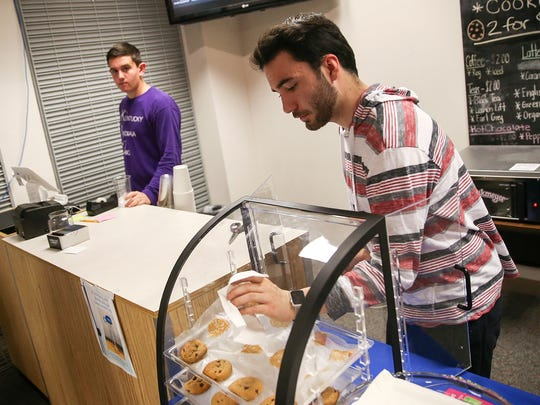 At right, senior Ethan Perkins, 18, serves cookies at the Carmel Cafe and Market run by DECA students at Carmel High School, Thursday, May 4, 2017. Students have been self-running the coffee shop and spirit-wear business for three years, based on a plan designed for class by two Carmel high alumni. Perkins designed the smartphone app that delivers cafe drinks and treats to classes.
