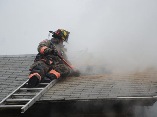 Firefighters cut open the roof to reach the fire in the attic of a farmhouse in Newton Township Tuesday, Oct. 24, 2017.