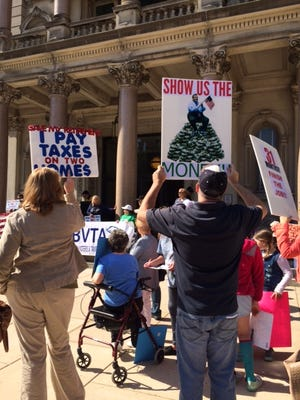 Ocean County Sandy survivors hold up signs at a rally Thursday outside the Statehouse in Trenton.