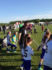 Getting his Clawson Strikers 06 girls ready to face the Troy SC Lynx in their first-ever Canton Cup game is coach Dave Jagodzinski.
