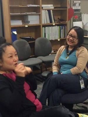 Henny Ohr, left, a Korean-born lawyer and head of day-to-day operations at EMBARC, Ethnic Minorities of Burma Advocacy and Resource Center, speaks with board president Mone Aye.
