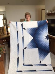 "Marguerite Richards, 78, named quilter of the year by the Mansfield Millennium Quilt Guild, proudly held ""Vern's quilt,"" a quilt she worked on for two years for her husband."