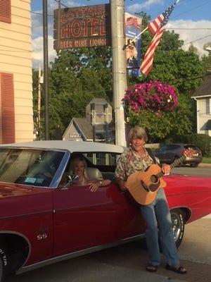 Hilary Stott, in the car, has owned and operated the Cottage Hotel in Mendon for a decade with her husband, David. Also pictured is musician Paul Strowe, who frequently performs at the Cottage.