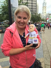 Reporter Maureen Gilmer shows off a souvenir Pope Francis doll that student Lauren Smith bought in Philadelphia.
