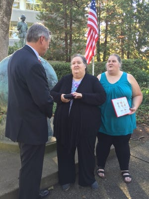 U.S. Sen. Jeff Merkley presents replacement medals to wife Susan Crom and daughter Robin Crom in front of the VFW Veterans' Memorial on the grounds of the Oregon Department of Veterans' Affairs in Salem.