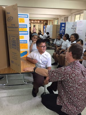 Lt. Gov. Ray Tenorio, right, speaks with Mount Carmel Middle School student Aiden Charfauros Tuesday during the school's first business fair. Students submitted more than 100 business proposal and plan entries, describing and promoting new and creative business ideas.