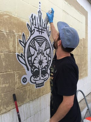 Brandon Barnhart, graphic designer and member of Art Beyond Walls prepares a portion of the Day of the Dead inspired imagery on the side of First City Art Center for the Gonzalez St. Project that will take place on Tuesday.