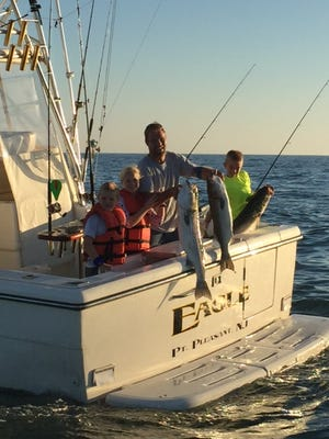 Dave Carman with his three kids: Danny (age 11); Emmy (age 9); Dalton (age 7) with four striped bass between 18 to 26 pounds.
