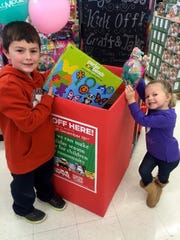 Children drop off new toys for the U.S. Marine Corps Toys for Tots drive at A.C. Moore Arts and Crafts in Asheville. Toys for Toys boxes are at popular shopping destinations around town.