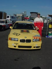 Dave Hogg, CEO of Springwood Hospitality, photographed next to his racecar in 2002 before his first race at Watkins Glen Raceway.