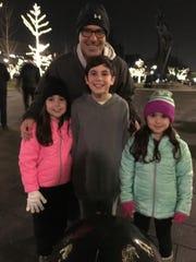 Jeff Schoenberg and his three children, Cooper, Dylan and Jordan, enjoy the menorah lighting at Shain Park.