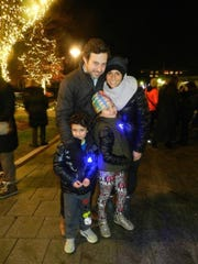Traci and Dustin Feldman with their two children, Charlie and Laila, enjoy the menorah lighting at Shain Park.