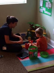 Patrick Angel, 3, with one of his therapists at the