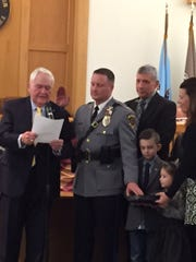 Toms River police Capt. James Harris (center) takes the oath of office from Toms River Mayor Thomas F. Kelaher (l) on Tuesday.