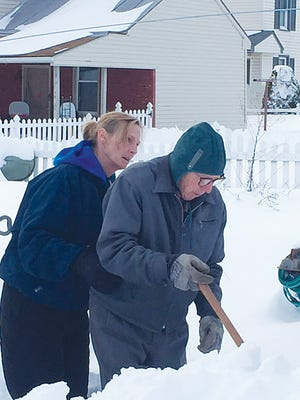 Susan Tipton, owner of Seniors Helping Seniors, helps one of her clients as he gets out in the snow.