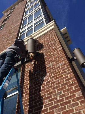 Brett Beaber of New Wave Security in Raleigh installs security lighting on the new Hyatt Place Hotel in downtown Asheville. The hotel boom has helped support hundreds of jobs.
