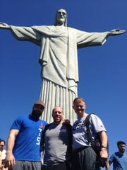 USA Weightlifting's Colin Burns, left; Travis Cooper, center; and Dr. Mark Lavallee post in front of the Christ the Redeemer statue in Brazil.